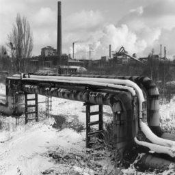 krajobraz przemysłowy, na pierwszym planie rury ciepłownicze, w tle dymiące kominy