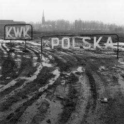 Rozjeżdżone przez samochody błoto, koleiny wypełnione wodą. W tle konstrukcja metalowa z nazwą dawnej kopalni. Napis KWK Polska.