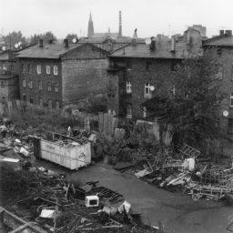 Składnica złomu. Zabudowania poprzemysłowe , masywne budynki ceglane, w oddali wieża kościoła i komin ciepłowni.