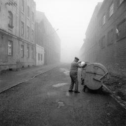 Ulica między dwoma rzędami starych kamienic, po lewej stronie mężczyzna wrzuca coś z jasnego kubła, do metalowego kontener na śmiecie.