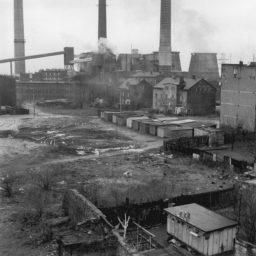 Krajobraz postprzemysłowy, w tle kominy , na pierwszym planie puste place i zabudowania.